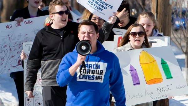 Brock Doemel leads a newly formed gun violence prevention group in Oshkosh called Students Against School Shootings (SASS) as participants walks along Main Street Friday in Oshkosh, Wisc. marching toward Senator Ron Johnson's office on April 20, 2018.