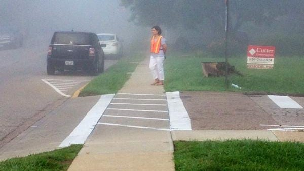 A school crossing guard awaits students in the fog.