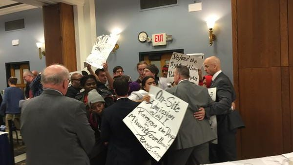 Protesters interrupt a Regents meeting at the University of Michigan today.