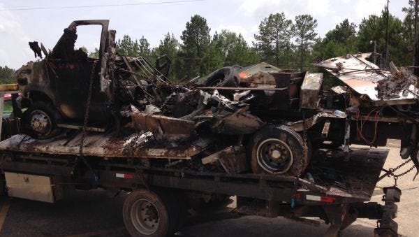 The remains of the burned-out ambulance are seen on a truck.