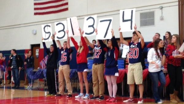 Appleton East Key Club members and football players announce how much money Appleton Tackles Cancer raised during the Homecoming pep rally Friday.