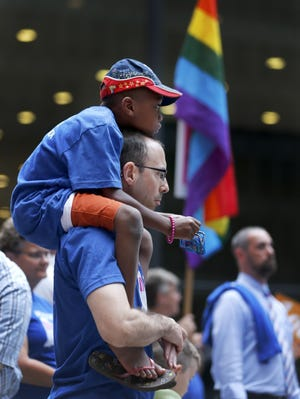 George Sloan, from Chicago, holds his son, Sloan D'Souza, on his shoulders as they attend a rally in support of gay marriage in Wisconsin and Indiana, at the federal plaza Monday, Aug. 25, 2014, in Chicago. The Chicago-based 7th U.S. Circuit Court of Appeals will hear arguments Tuesday on gay marriage fights from Indiana and Wisconsin, setting the stage for one ruling. Each case deals with whether statewide gay marriage bans violate the Constitution.