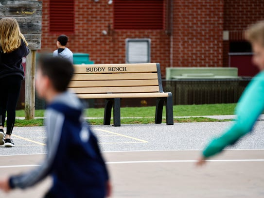 A buddy bench sits just off the basketball courts during
