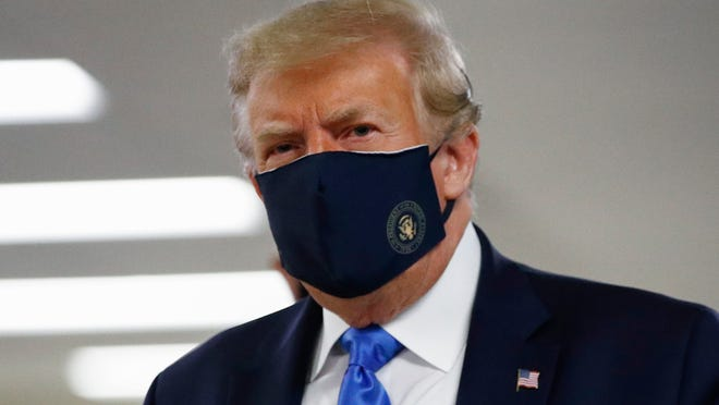 President Donald Trump wears a face mask as he walks down a hallway during a visit Saturday to Walter Reed National Military Medical Center in Bethesda, Md.