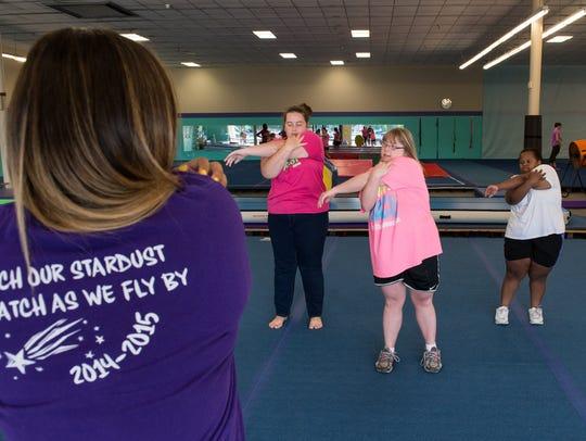 Cheerleading coach, Katya Andrews, left, instructs