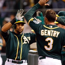Aug 23, 2014; Oakland, CA, USA; Oakland Athletics center fielder Coco Crisp (4) high fives left fielder Craig Gentry (3) and teammate after scoring a run against the Los Angeles Angels during the eighth inning at O.co Coliseum.