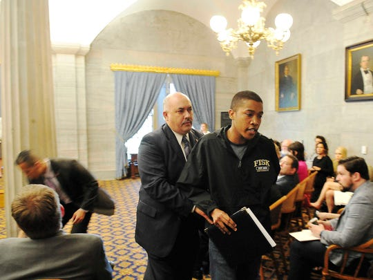 Justin Jones, a Fisk University student, is escorted out as Gov. Bill Haslam and House Speaker Beth Harwell make a health care announcement at the state Capitol on April 12, 2016, in Nashville.