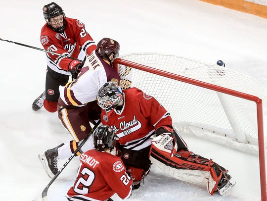 Will Borgen (20) of St. Cloud State pushes Neal Pionk