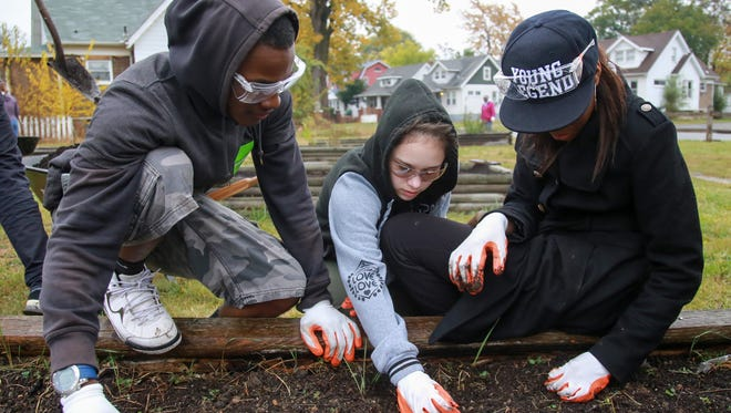 Volunteers from Public Allies volunteer to winterize the Focused Hands community garden on Make A Difference Day in Detroit, on Saturday, Oct. 24, 2015.
