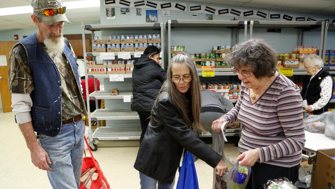 Volunteer Mary Mosson, right, holds a sack open as Darrell and Theresa Wallace select from fresh fruits and vegetables Tuesday, December 16,  2014, at the Bauer Community Center food pantry, 330 Fountain Street in Lafayette. Clients are allowed to visit the food pantry once a month. The food pantry at Bauer Community Center is being pushed out of the building. Bauer officials came to the pantry leaders, Church Women United, in July and told them then had one year. Now, due to reshuffling of space at Lafayette School Corp., tied to Task Force VI, the time table is being moved up. By February, Bauer wants the pantry gone or at least know when they will be relocated. The pantry has been in Bauer for 35-40 years.