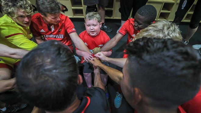 David Turner participates in a team huddle in the locker room with the Louisville soccer team on Thursday afternoon.    Turner, 6, has an inoperable brain tumor.  The team gave him a jersey and had him participate in a shootout that he helped to win.June 14, 2018