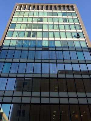 A crew from Great Lakes Window Cleaning cleans the outside of the windows at the Farnum Building Wednesday, November 4, 2015, in downtown Lansing.