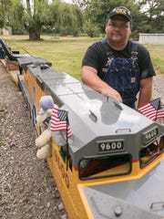 Dan Kalis poses next to one of his gas-powered locomotives