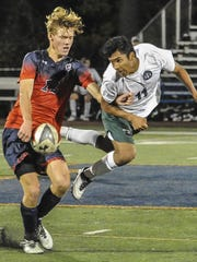 Mendham's Hans Gallagher (12) and Delbarton's Ivan Ruiz (11) battle for possession in the Morris County Tournament final.