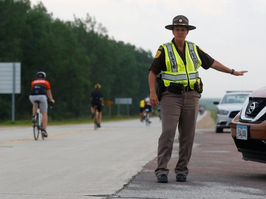 Trooper Shelby McCreedy stops a car as riders make their way along the route between Thornton and Swaledale Wednesday, July 26, 2017, on the fourth day of RAGBRAI.