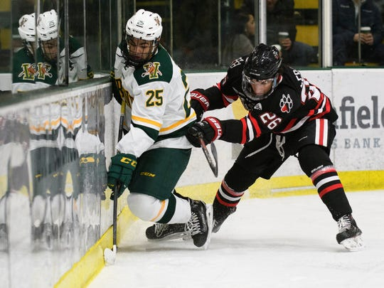 Norhteastern's Biagio Lerario (26) battles for the puck with Vermont forward Matt Alvaro (25) during the men's hockey game between the Northeastern Huskies and the Vermont Catamounts at Gutterson Fieldhouse on Friday night February 16, 2018 in Burlington.