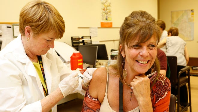 Public health nurse Barbara White gives Lynne Bonelli of Stony Point, N.Y., a flu shot at the Rockland County Health Department in Pomona, N.Y., on Friday, Oct. 2, 2015.