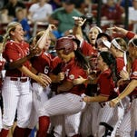 Leona Lafaele is mobbed at home plate after hitting a two-run home run against Kentucky for the game's only runs on Friday.