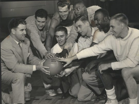 Milwaukee Hawks players smile at Coach Doxie Moore