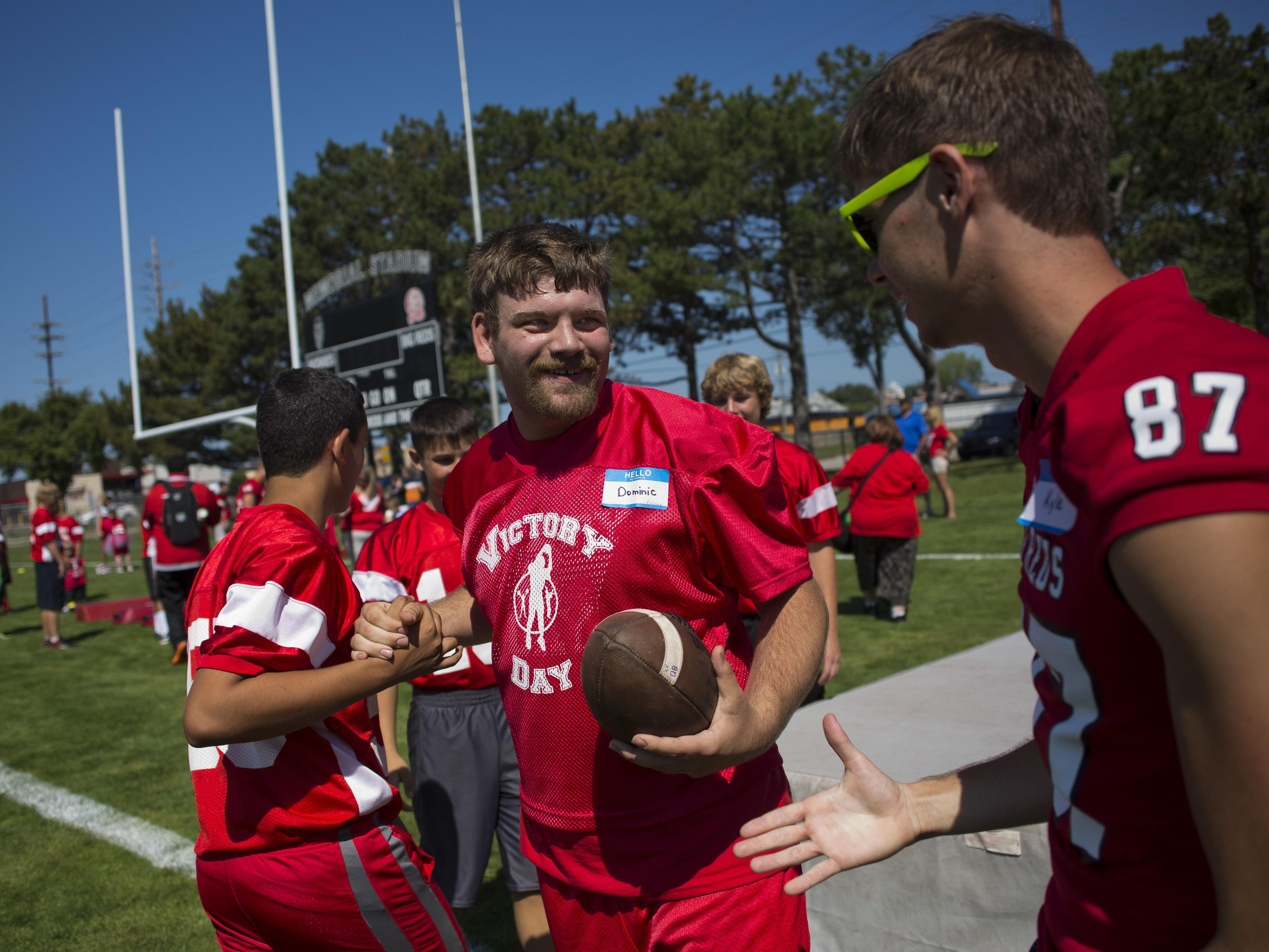 Dominic Pelione gets high-fives after running a skills drill with players during Victory Day Saturday, August 15, 2015 in Memorial Stadium at Port Huron High School. The event paired special needs students with mentors from the football and cheerleading teams.