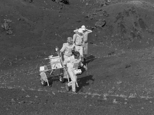 """This 1970 image provided by NASA shows Apollo 14 astronauts Alan Shepard, Edgar Mitchell and Stuart Roost and an unidentified man training with a Modularized Equipment Transporter on the Big Island of Hawaii. Before many Apollo astronauts went to the moon, they came to Hawaii to train on the Big Island's lunar landscapes. Now, decades-old photos are surfacing of astronauts scooping up Hawaii's soil and riding across volcanic fields in a """"moon buggy"""" vehicle."""