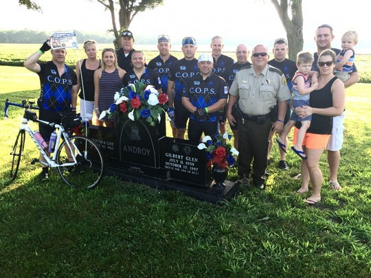 Family of Gilbert Glen, local law officers and the Iowa C.O.P.S. RAGBRAI team gather around Glen's grave outside of Malvern.
