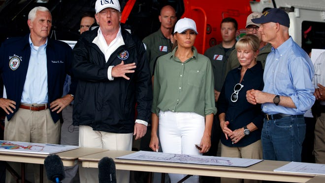 President Donald Trump, first lady Melania Trump and Vice President Mike Pence, left, participate in a briefing on the Hurricane Irma relief efforts, Thursday, Sept. 14, 2017, in Ft. Myers, Fla., after arriving at Southwest Florida International airport. (AP Photo/Evan Vucci)