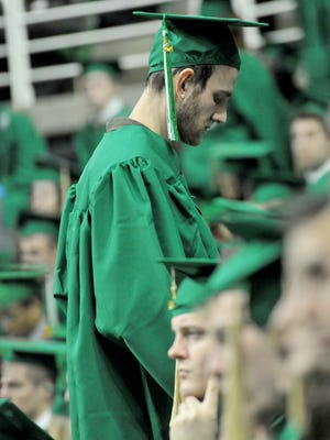 One of about 18 MSU seniors who turn their backs as conservative columnist George Will speaks to the graduates at commencement Saturday, December 13, 2014.