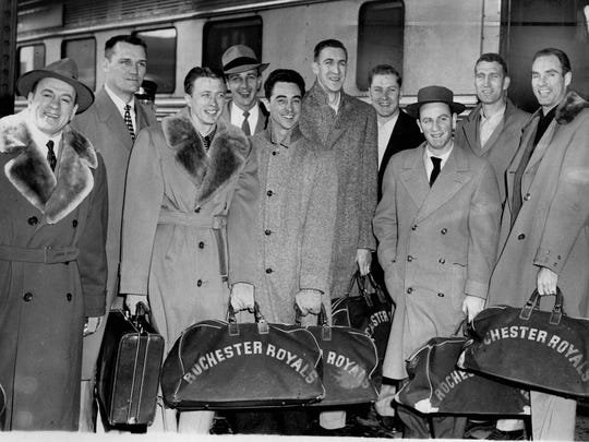 Rochester's Royals, carrying Western Division championship they won on road, got back in town after six-day jaunt. From left, as they stepped off train, owner-coach Les Harrison, Arnie Johnson, Bob Davies, Odie Spears, Bob Wanzer, Arnie Risen, Ray Ragelis, Red Holzman, Jack Coleman, Alex Hannum. 1952.
