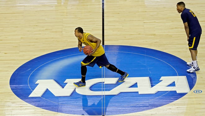 West Virginia's Jevon Carter pushes the ball across mid court as Tyrone Hughes watches, right, during practice for a college basketball regional semifinal game in the NCAA Tournament in Cleveland, Wednesday, March 25, 2015. West Virginia plays Kentucky on Thursday. (AP Photo/Tony Dejak)