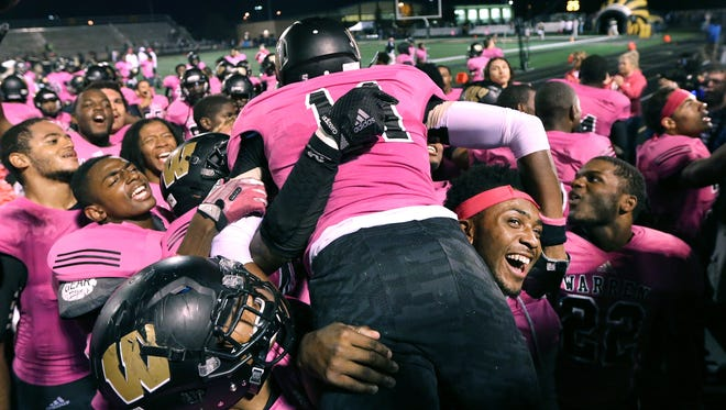 Warren Central players lift up teammate Wilmer Cole after Friday night's 28-21 win over Ben Davis at Warren Central High School on September 19, 2014. Cole intercepted the pass that saved the game late in the fourth quarter.