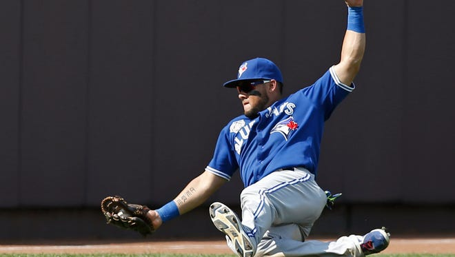 Toronto Blue Jays left fielder Melky Cabrera makes a sliding catch of Ichiro Suzuki's ninth-inning fly ball to deep left field in Sunday's game at Yankee Stadium.  The Blue Jays defeated the Yankees 5-4.