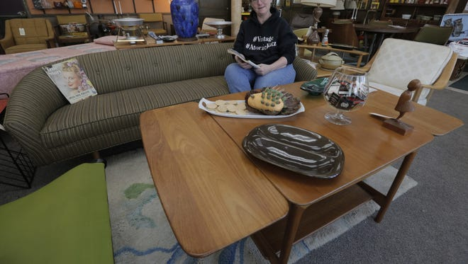 Deb Toman co-owner of AtomicKatz, in Oshkosh, Wis. sits on a mid-century modern couch.  Her store is surrounded by the design and décor of the 1950s to mid 1970s from chairs, ashtrays, tables, lamps and entertainment of the era. Joe Sienkiewicz / USA TODAY NETWORK-Wisconsin
