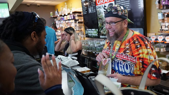 'Budtender' Jason Coleman describes the effects of a marijuana-infused lubricant to customers inside the Medicine Man cannabis dispensary in Denver on April 19, 2017. Thousands of marijuana tourists are visiting Denver -- and stocking up in stores like Medicine Man -- for the annual 420 celebration.