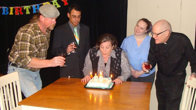 "Grandma Rose, played by Donna Johnson, blows out the candles on her 80th birthday cake, watched by Seamus O'Riley (George Straka), Conor McFadden (Marcel Bruyere), Nurse Kelly (Keri Grimsley) and Fr. Mike (Dan Sallinen) in a scene from the Rogue Theater production of the audience-participation murder mystery ""Eat, Drink, and Be Murdered.""  The production has five dinner shows and two non-dinner shows scheduled in April."