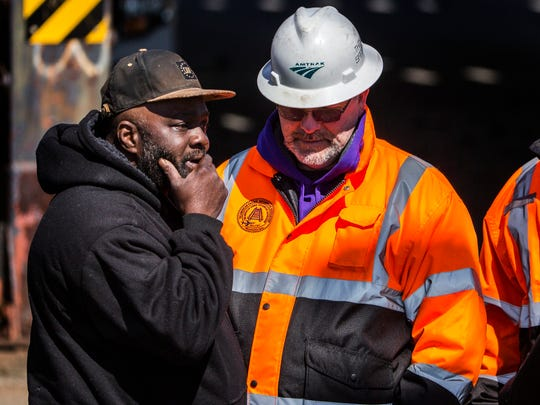 A family member reacts after learning his brother was one of two people killed after an Amtrak train struck a piece of construction equipment on the tracks in Chester, Pa. on Sunday morning.