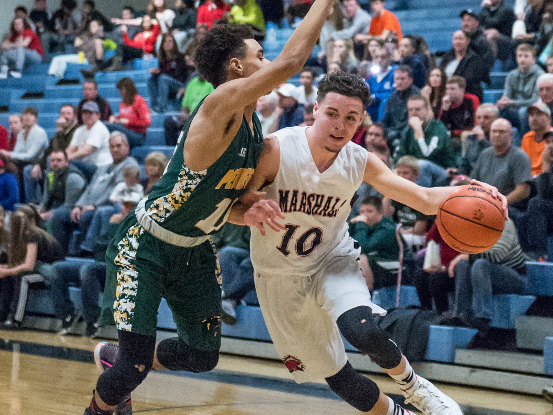 Marshall's Jacob Brubacker (10) drives to the basket against Pennfield's Francois Jamierson (11 ) during Monday's district game.