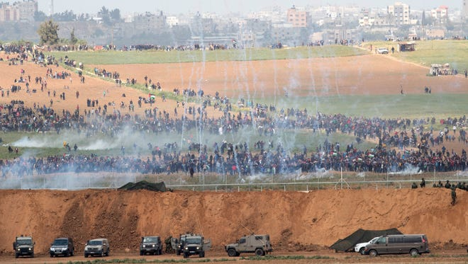 Israeli troops fire tear gas towards Palestinian protesters marching towards the Israeli Gaza border near Nir Am and next to the Gaza town of Beit Hanun, on March 30, 2018.