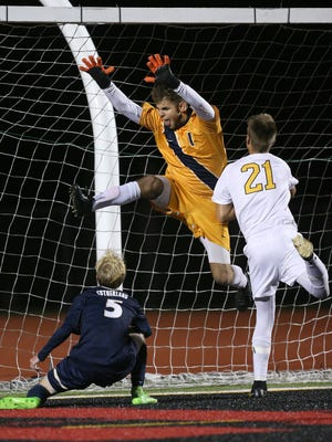 Pittsford Sutherland goalie Alex Oleyourryk leaps over teammate Johah Pierce (5) to cover the goal against Honeoye Falls Lima's Hayden Smith (21) during the Class A2 final.