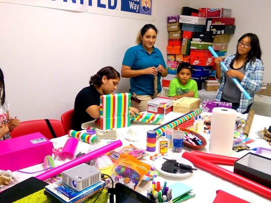 United Way volunteers assemble Shoebox care packages for the homeless.
