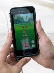 """Doduo, a Pokemon, is found by a group of  Pokemon Go players, Tuesday, July 12, 2016, at Bayfront Park in downtown Miami. The """"Pokemon Go"""" craze has sent legions of players hiking around cities and battling with """"pocket monsters"""" on their smartphones. It marks a turning point for augmented reality, or technology that superimposes a digital facade on the real world. (AP Photo/Alan Diaz)"""