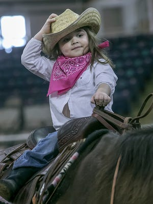 Maddy Roe holds onto her hat as she gets a ride on a horse at the Rutherford County Sheriff's Office SRO Rodeo at the Tennessee Miller Coliseum.