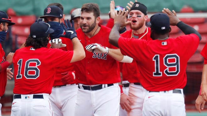 Boston Red Sox's Mitch Moreland, center, celebrates his two-run, walk-off home run during the ninth inning of a baseball game against the Toronto Blue Jays, Sunday, Aug. 9, 2020, in Boston.