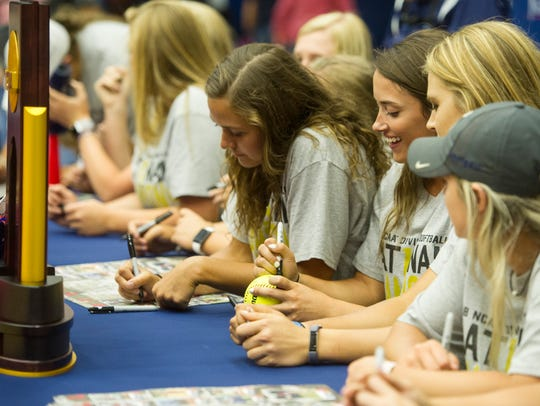 Softball players sign posters and balls during the