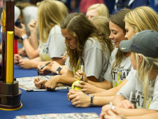 Softball players sign posters and balls during the USI Softball National Champion homecoming rally on Wednesday, May 30.