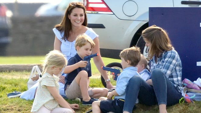 Prince George plays with a toy gun during a charity event June 10 in England with his mother, Catherine, Duchess of Cambridge.