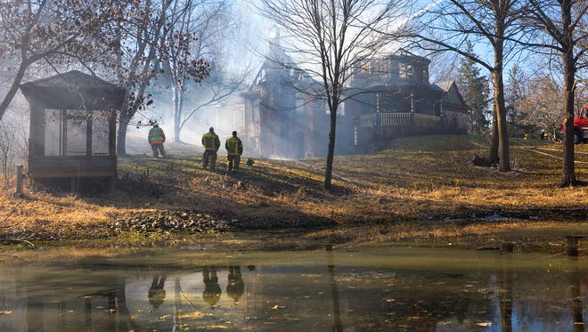 A St. Joseph ladder truck sprays water down on a house fire as other firefighters watch Thursday afternoon, March 24, in Collegeville Township. Avon, St. Joseph, Albany, and Cold Spring fire departments were called to the fire on 160th Avenue near 315th Street south of Avon.
