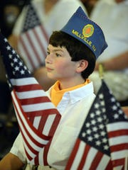 Zach Asselta, a member of the Sons of the American Legion, is surrounded by American flags during a 9/11 remembrance ceremony at the Millville Fire Station on Thursday, September 11, 2014.  Staff photo/Charles J. Olson