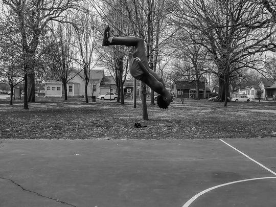 Nick Johnson, 18, pulls off an acrobatic tumbling maneauver for friends after a pickup game of basketball at Indianola Park on Indy's Near West side on Tuesday, March 21, 2017.