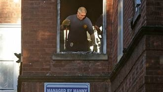 A fire marshal sifts through debris in an apartment building where four children died in an early morning fire today in Chicago. Two adults were also injured in the blaze and about 50 other residents escaped the fire.